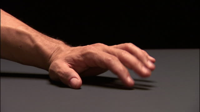 Close up studio shot of man's hand drumming fingers on surface