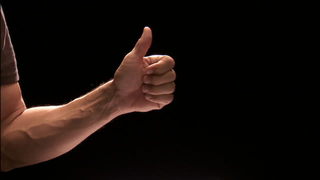 Close up studio shot of man's hand giving thumbs-up sign