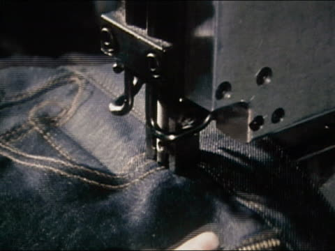 1980 close up studs being punched into pocket of denim jeans at jeans factory / AUDIO