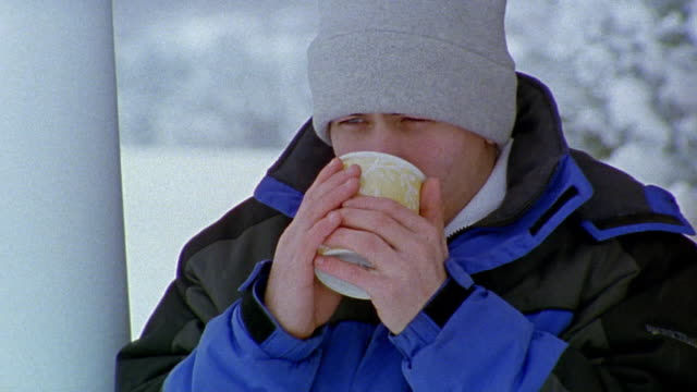 Close up teenage boy drinking hot chocolate outdoors