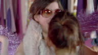Close up teenage girl playing dress-up with fur around neck, shaking pom poms and putting on sunglasses/ pan two other girls trying on sunglasses in mirror