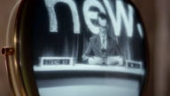 Close up television newscaster on old black and white television / reception breaks up