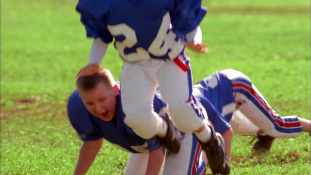 Close up three young boys wearing football uniforms exercising and jumping to ground