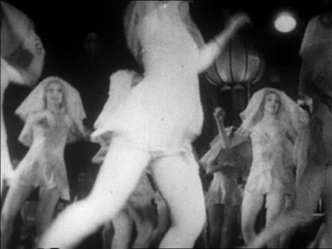 B/W 1928 close up tilt down legs of chorus girls doing kicks / newsreel