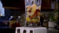 Close up tilt down orange juice being poured into blender filled with fresh fruit / blender being turned on to make smoothie