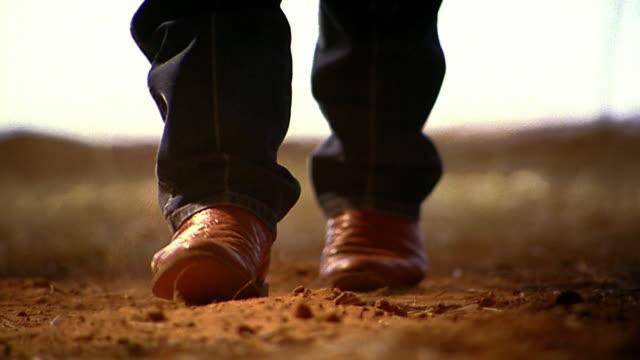 Close up tilt down rack focus legs and cowboy boots walking on dusty dirt