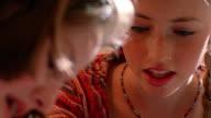 close up tilt down tilt up teenage girl painting other teenage girl's toenails indoors