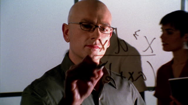 Close up tilt up bald man writing algebraic equation on transparent surface in front of him / people pass background