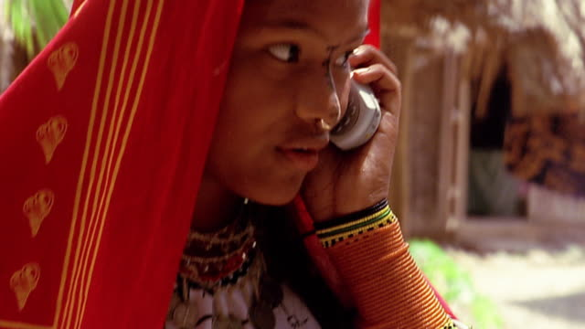 Close up tilt up from hand dialing cellular phone to girl in traditional dress talking on phone / Panama