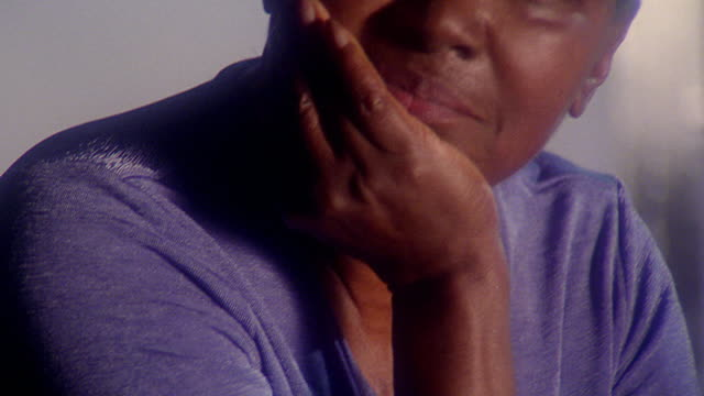 close up tilt up PAN PORTRAIT Black woman sitting with hand on chin indoors