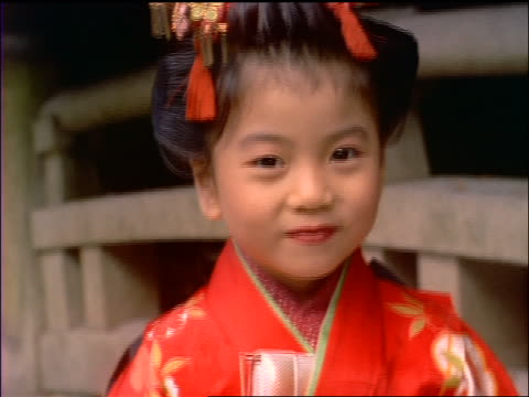 close up tilt up PORTRAIT small Japanese girl in traditional dress looking at camera / Japan