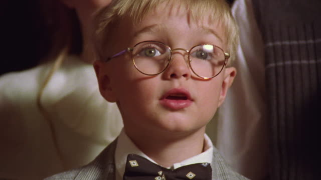 Close up tilt up small blonde boy with eyeglasses and bow tie talking + singing indoors