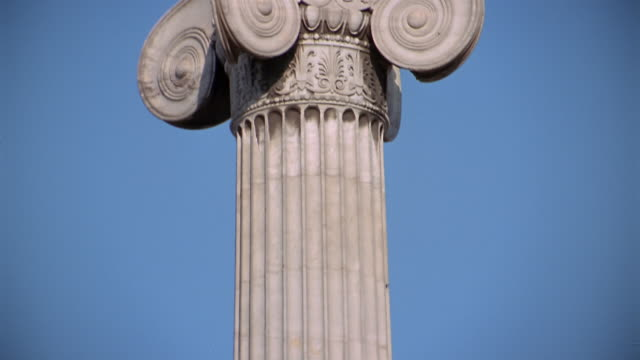 Close up tilt up statue of Apollo on top of a column at Athens Academy / Athens, Greece