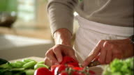 Close up tilt up tilt down from hands to face of man slicing tomato on cutting board / Belgium