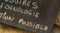 Close up tilt up tilt down rack focus pan wine store chalk board sign with French writing / Provence, France