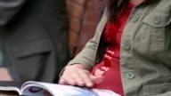 Close up tilt up woman reading magazine at outdoor cafe / Milwaukee, Wisconsin