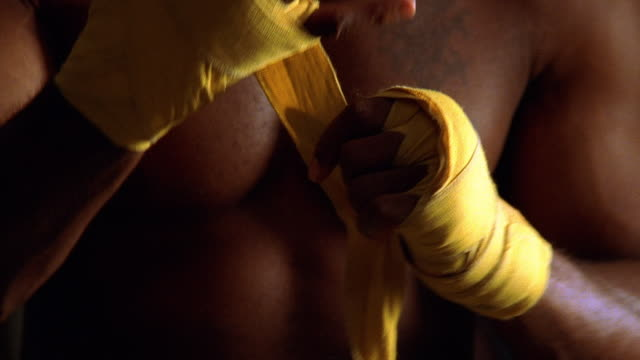 close up tilt up zoom out shirtless Black male boxer wrapping his hand with yellow tape in locker room