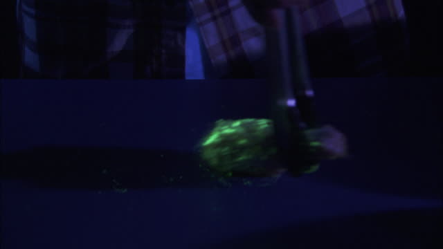 Close Up tilt-up - A food worker bastes a contaminated chicken wing under a black light
