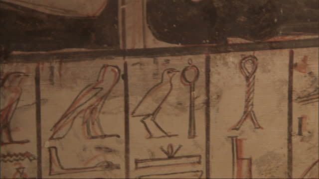 Close Up, tilt-up - A mural depicts Egyptian figures and hieroglyphics
