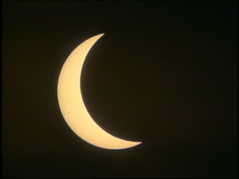 close up time lapse solar eclipse moving to + past totality with clouds partially obscuring view / Austria 1999