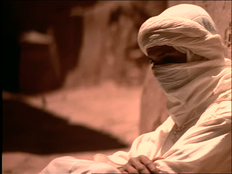 close up PAN to Middle Eastern man in turban sitting against wall + turning head to camera / Morocco