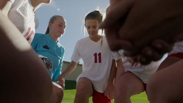 Close up to wide slow motion panning shot of soccer players praying / Springville, Utah, United States