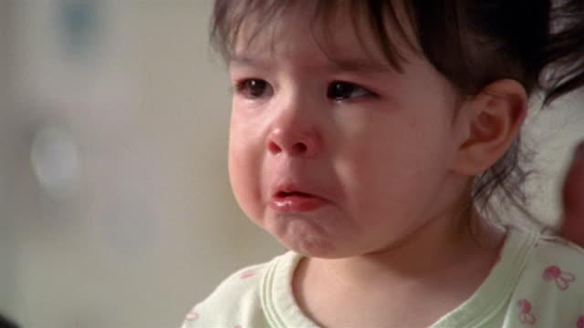 Close up toddler crying / tilt up doctor listening through stethoscope / tilt down toddler / El Paso, Texas