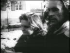 B/W 1956 close up tracking shot couple walks to Austrian border / exiting Hungary after revolution / newsreel