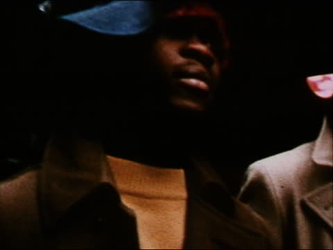 1970 close up tracking shot gang members walking slowly in alley wearing hats