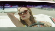 Close up tracking shot of beautiful woman driving convertible car / Pleasant Grove, Utah, United States