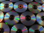 close up tracking shot over rows of CDs on table covered with black cloth