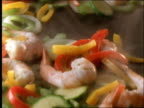 close up tracking shot over stir-fry shrimp and vegetables cooking