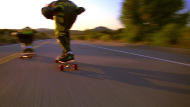 close up tracking shot REAR VIEW two skateboarders with helmets speeding on mountain road