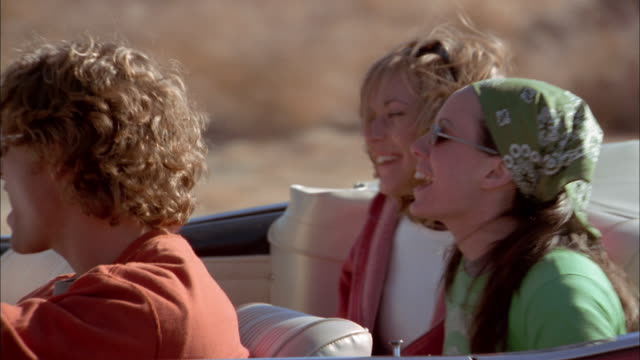 Close up tracking shot young women checking maps in back seat of convertible / losing and catching map