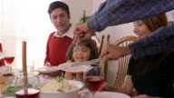 Close up turkey being served to family for Christmas dinner / boys holding plates while turkey is carved