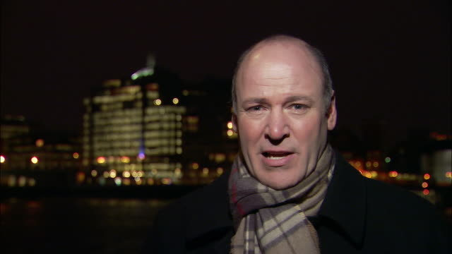 Close up TV reporter talking to camera outside at night/ London