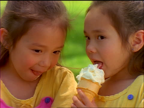 close up twin Korean girls sharing ice cream cone outdoors