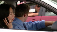 Close up two frustrated drivers commiserating in traffic jam / passenger talking on cell phone