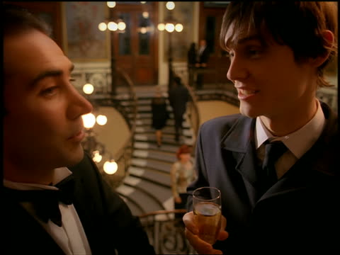 Close up two men in formalwear talking and holding champagne with people ascending ornate staircase in background