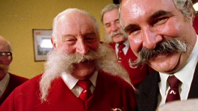 Close up two senior men with elaborate mustaches toasting pints of beer