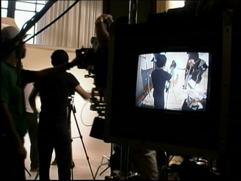 Close up video monitor view of photographer, crew and female model on set of fashion shoot in studio