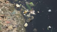 Close Up view of all kinds of garbage floating in the river Citarum