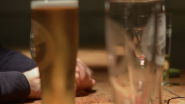 Close up view of drinking glasses in and in traditional English pub friend socialise and enjoy an animated conversation