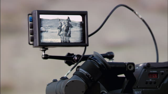 Close up view of scene in camera monitor / cinematographer looking through viewfinder / view of cinematographer walking up to director talking to actors / cinematographer coming back to looking through camera / Red Rock Canyon State Park, California
