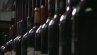 close up wide shot bottles standing on rack of wine cellar focus pull close up row of red wine bottles / pan red wine cellar