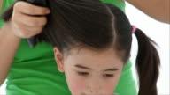 Close up woman brushing daughter's hair/ Brooklyn, New York