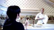 Close up woman drinking at bar / man walking up and talking to her / woman walking away