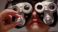 Close up woman getting eye examination with optometry equipment / doctor's hand adjusting dial