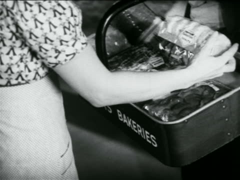 B/W 1938 close up woman inspecting doughnuts + other baked goods in basket / industrial