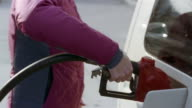 Close up woman pumping gas into tank of SUV at gas station